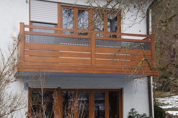 Staketto-Horizontal Balkon - mit Füllungsstäben in Holzdekor, 150 unter und 60 über Zierfeld mit Lochblechfüllung. Balkonverblendung als Extra.