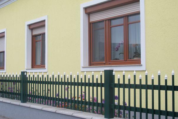 Palisaden Zaun mit Spitzkappen - in Farbe wie Steherkappen, abgesetzte Oberkante.