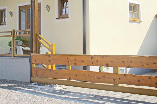 Rahmen Schiebetor & Glasal Geländer  - Schiebetor mit E-Antrieb und Holzlatten.